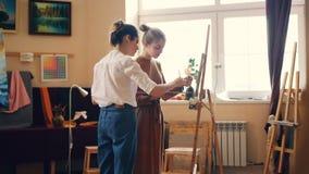 De aantrekkelijke studente schildert tijdens kunstklasse in studio, komt haar leraar en bevordert haar het onderwijs het geven stock video