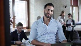 De aantrekkelijke succesvolle gemengde ras chef- zitting in het bureau, die aan een laptop computer werken, onderzoekt de camera  stock video