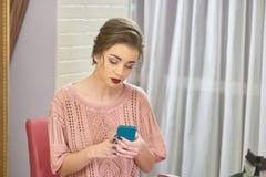 De aantrekkelijke telefoon van de vrouwenholding stock afbeelding