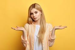De aantrekkelijke verwarde blonde vrouw is uitdrukking niet bevallen, royalty-vrije stock foto