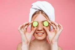 De aantrekkelijke vrolijke die vrouw met een handdoek rond haar hoofd wordt verpakt, die komkommer houden snijdt dichtbij haar og stock foto's