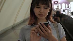 De aantrekkelijke vrouw berijdt neer roltrap aan metro gebruikend een smartphone stock videobeelden