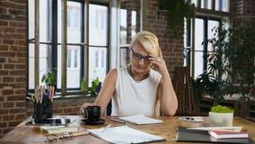 De aantrekkelijke vrouw controleert rapportering in de agenda terwijl koffiezitting achter het bureau in huisbureau drinkt binnen stock footage
