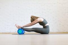 De aantrekkelijke vrouw die het typische uitrekken, hoofd aan knieën met schuim blauwe rol doen zich, paschimottanasana stelt, bi royalty-vrije stock afbeelding