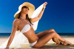 De aantrekkelijke vrouw in een bikini glimlacht bij de zon bij het strand Royalty-vrije Stock Foto's