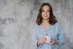 De aantrekkelijke vrouw gekleed in nachthemden, houdt witte mok met koffie of de thee, heeft ochtenddrank, stelt binnen tegen vag royalty-vrije stock foto