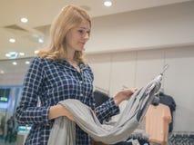 De aantrekkelijke vrouw kiest kleren in een winkel Het concept shopp Royalty-vrije Stock Afbeeldingen