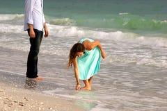 De aantrekkelijke vrouw in kleding buigt om shell op te nemen Stock Afbeeldingen