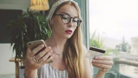 De aantrekkelijke vrouw maakt aankopen met creditcard en cellphone Wijfje die online in koffie winkelen stock videobeelden
