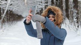 De aantrekkelijke vrouw in matroos met bont` s kap maakt selfie op haar mobiele telefoon in de winterpark stock videobeelden