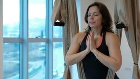 De aantrekkelijke vrouw mediteert padmasana stelt hangmat binnen in studio stock video