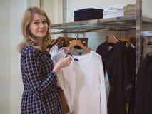 De aantrekkelijke vrouw met blond haar in een kledingsopslag kiest auto Royalty-vrije Stock Afbeeldingen