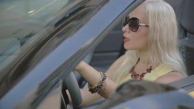 De aantrekkelijke vrouw met rode lippenstift begint de auto stock footage