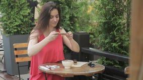 De aantrekkelijke vrouw neemt beelden van voedsel op telefoon in de zomerkoffie stock videobeelden