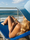 De aantrekkelijke vrouw ontspant op chaise-longue Stock Foto