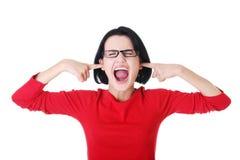 De aantrekkelijke vrouw in oogglazen zet haar vinger in oren. Stock Afbeeldingen