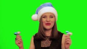 De aantrekkelijke vrouw in santahoed lacht, zingt Kerstmislied en danst tegen het groene scherm van chromakey stock videobeelden