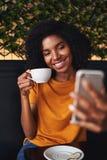 De aantrekkelijke vrouw in toevallige kleding neemt selfie in een koffiewinkel stock foto's
