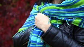 De aantrekkelijke vrouw verpakt zich omhoog met kleurrijke sjaal stock footage