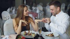De aantrekkelijke vrouw zegt ja aan aanzoek en haar vriend zet verlovingsring op haar vinger en stock footage