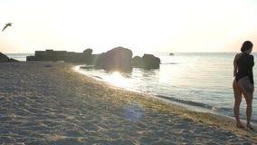 De aantrekkelijke vrouw in zwarte bodysuit met een mooi lichaam loopt op het zand op het strand na een training Fitness, sport, y stock videobeelden