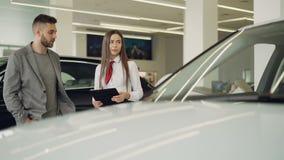 De aantrekkelijke vrouwelijke autohandelaar spreekt aan geinteresseerde klant over nieuw automobiel model en houdt documenten ter stock videobeelden