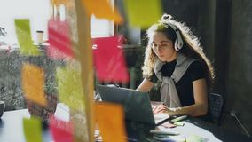 De aantrekkelijke vrouwelijke student luistert aan muziek met en hoofdtelefoons die terwijl het werken met laptop computer dansen stock footage