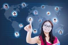 De aantrekkelijke vrouwelijke student verbindt met sociaal netwerk Stock Foto