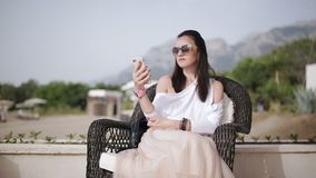 De aantrekkelijke vrouwenzitting als voorzitter in openlucht en gebruikt een smartphone stock video
