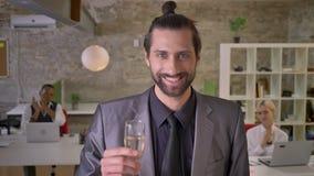 De aantrekkelijke zakenman met baard bevindt zich en houdend glas champagne in bureau, slaan de collega's, bedrijf stock video
