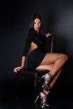 De aantrekkelijke zitting van de donkerbruine slijtage zwarte kleding op leerstoel Royalty-vrije Stock Afbeelding