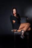 De aantrekkelijke zitting van de donkerbruine slijtage zwarte kleding op leerstoel Royalty-vrije Stock Afbeeldingen