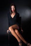 De aantrekkelijke zitting van de donkerbruine slijtage zwarte kleding op leerstoel Stock Foto's