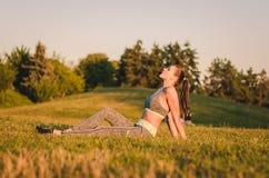 De aantrekkelijke zitting van de geschiktheidsvrouw op het gras in het park en Re Stock Foto's