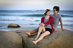 De aantrekkelijke zitting van het kustpaar op rots bij twili royalty-vrije stock fotografie