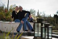 De aantrekkelijke zitting van het Paar door de pool Stock Afbeelding