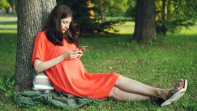 De aantrekkelijke zwangere vrouw in toevallige kleding gebruikt smartphonezitting op gras onder boom in park Zwangerschap, mensen stock footage