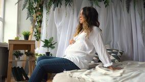 De aantrekkelijke zwangere vrouw zit in bed en houdt haar buik royalty-vrije stock foto