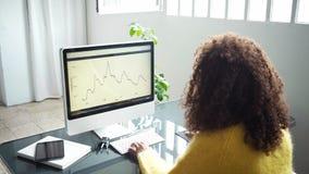 De aantrekkelijke zwartewerken aangaande computer in bureau stock videobeelden