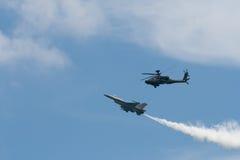 De aanvalshelikopter en een RSAF F-16C Fightin van RSAF ah-64 Apache Stock Fotografie