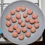 De aanvang van het koken van ruwe vleesballetjes op een pan over het fornuis royalty-vrije stock afbeelding