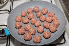 De aanvang van het koken van ruwe vleesballetjes op een pan over het fornuis royalty-vrije stock fotografie