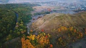 De aard van de de herfstochtend lucht videolengte Heuvel met weg en kleurrijke bomen Dorp op achtergrond Koude kleuren van stock videobeelden