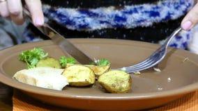 De aardappelen in de schil van de handbesnoeiing in de plaat Mes en vork in het kader stock video