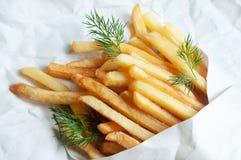 De Aardappels van aardappelsfrieten in een Witboekzak op een blad o Stock Foto