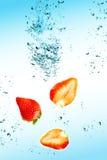 De aardbei valt in water met een grote plons Stock Foto