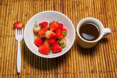 De aardbeien in kom en koffiekop, rotanachtergrond, selecteren foc Stock Afbeeldingen