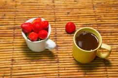 De aardbeien in kop en koffie, rotanachtergrond, selecteren nadruk bij Stock Fotografie