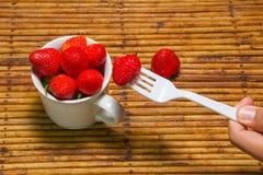 De aardbeien in kop, rotanachtergrond, selecteren nadruk bij strawberri Stock Fotografie