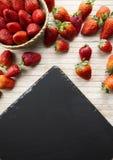 De aardbeien kopiëren ruimte met een kleine mand van aardbeien die door aardbeien worden omringd die op een houten bodem en een p royalty-vrije stock fotografie